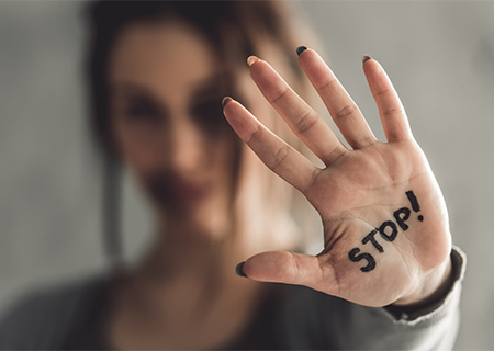 Woman holding up hand with the word Stop written on her hand