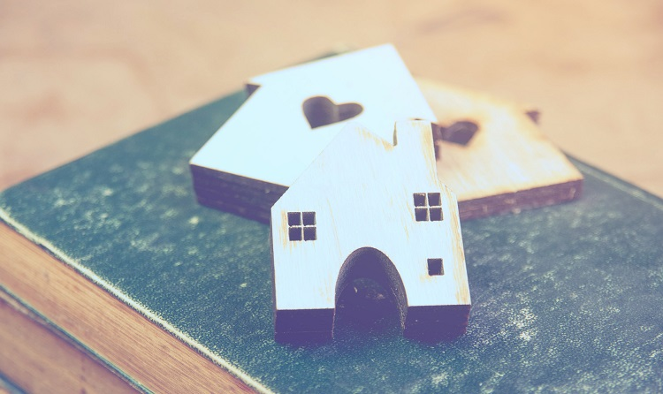 Wooden cut out in the shape of houses on top of an old book