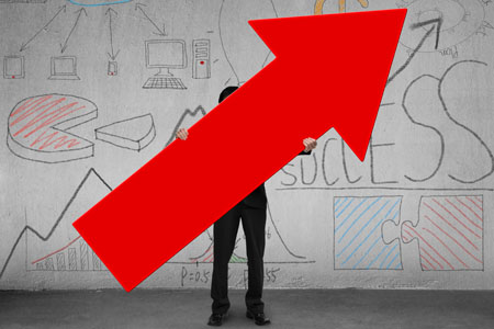 Business man holding up large red arrow