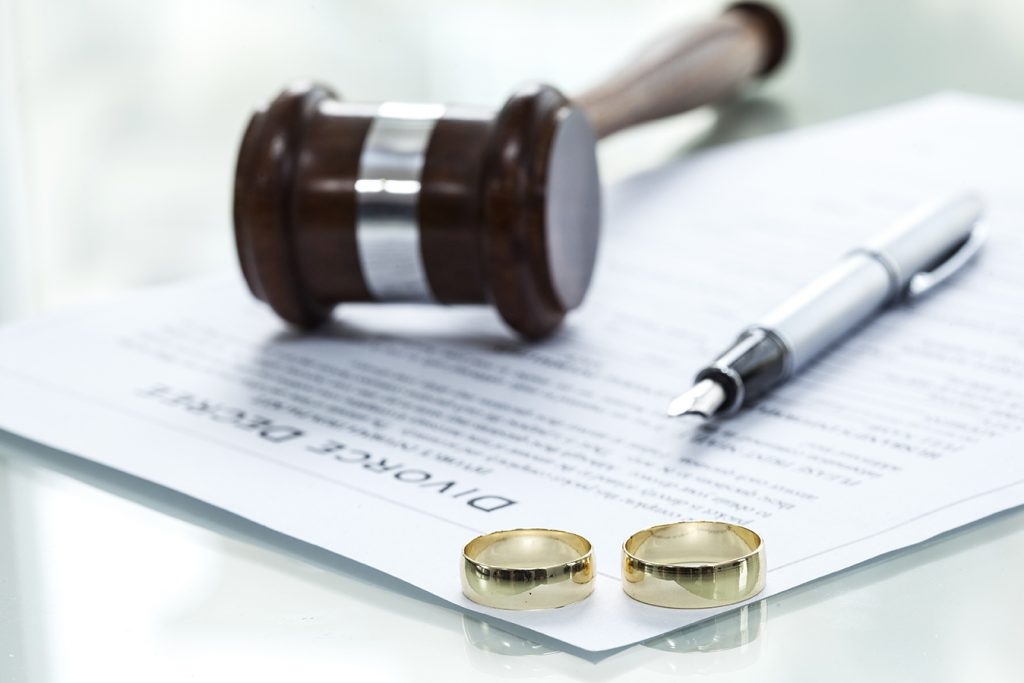 Judges hammer, two gold rings and a pen on top of divorce papers