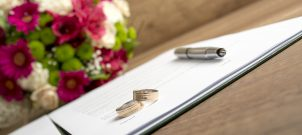Wedding bands and a pen sitting on paper next to flowers