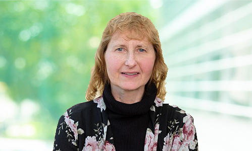 Dr. Kim E. Miller headshot green background