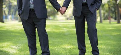 Two men holding hands representing a civil union