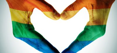 Heart made out of hands in LGBTQ flag colors.