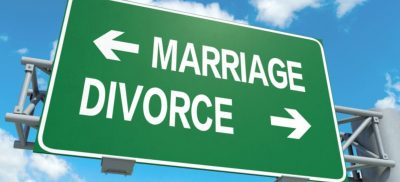 Road sign displaying marriage one way and divorce the other way.